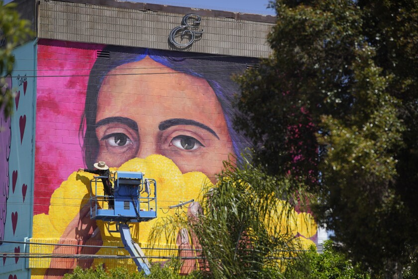 Local artist Tatiana Ortiz Rubio paints a 45-foot mural on the wall of Bread and Salt, titled Stop the Spread.