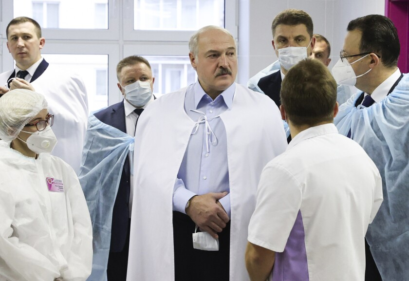Belarusian President Alexander Lukashenko, centre, listens to medics as he visits a transfusiology center in Minsk, Belarus, Friday, Nov. 27, 2020. (Maxim Guchek/BelTA Pool Photo via AP)