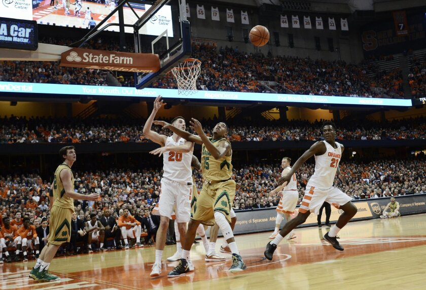 Notre Dame's Bonzie Colson, center, watches as the ball flies overhead after an attempt at a basket was thwarted by Syracuse's Tyler Lydon (20) during the first half of an NCAA college basketball game at at the Carrier Dome in Syracuse, N.Y., Thursday, Jan. 28, 2016. (AP Photo/Heather Ainsworth)