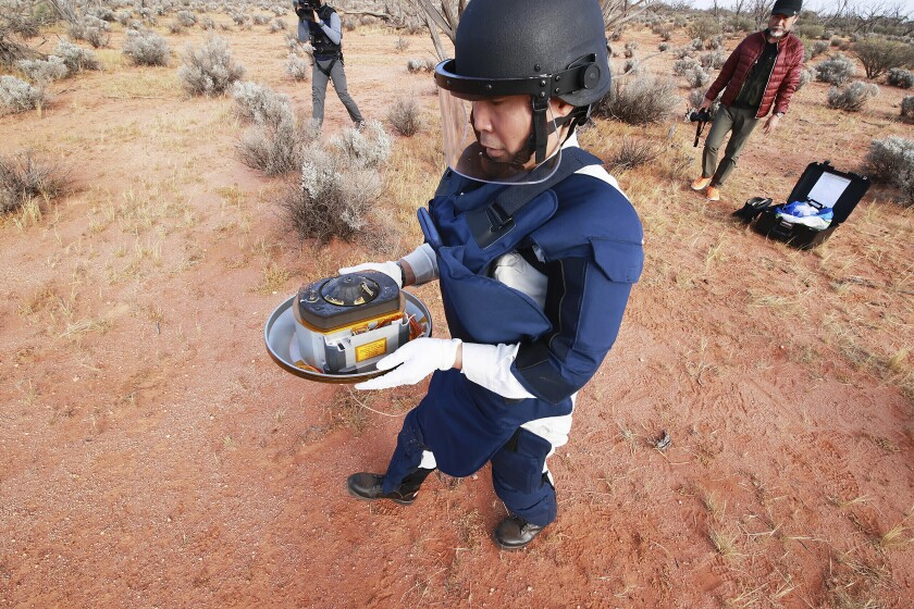 FILE - In this Sunday, Dec. 6, 2020 photo provided by the Japan Aerospace Exploration Agency (JAXA), a member of JAXA retrieves a capsule dropped by Hayabusa2 in Woomera, southern Australia. The small capsule from Japan's Hayabusa2 spacecraft successfully landed in a sparsely populated desert in the Australian Outback on Sunday. (JAXA via AP, File)