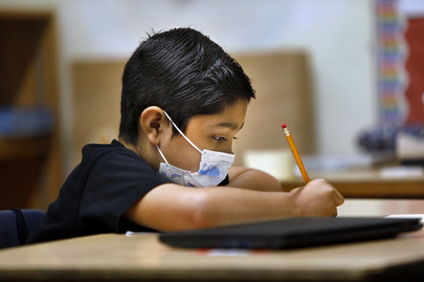 Third-grader David Cortez wears his mask during class while writing