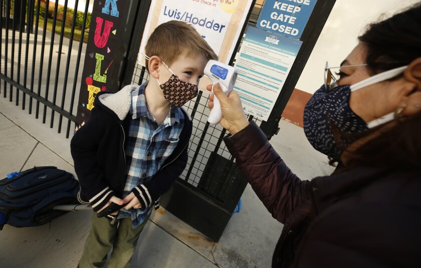 A boy rolling a backpack and wearing a mask stands as a woman holds a thermometer to his forehead.