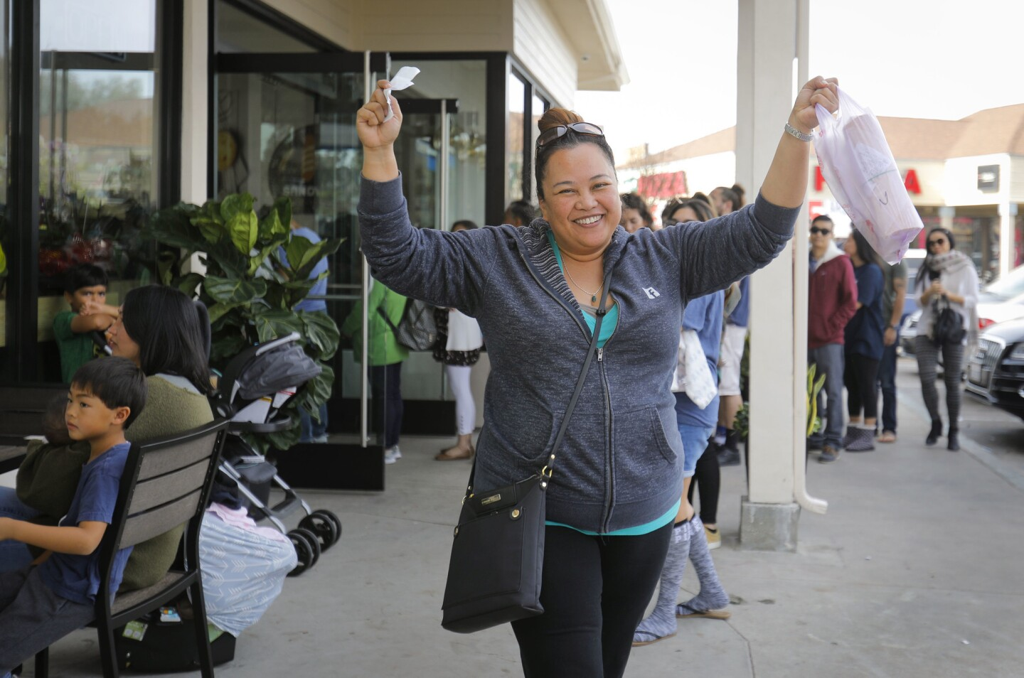 Joy Alcalen of Eastlake in Chula Vista is all smiles as she leaves K Sandwiches in Kearny Mesa with her order after waiting more than two hours during a visit on the second day of the grand re-opening.