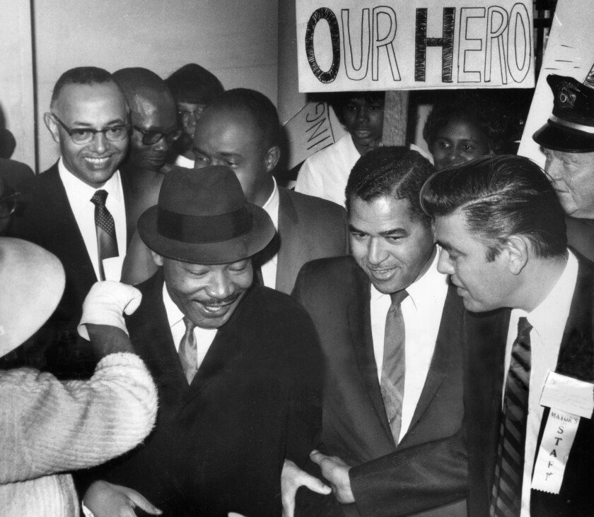 The Rev. Dr. Martin Luther King Jr., seen in Los Angeles in 1965, advocated that a racially divided America come together in community. President Trump stokes divisions.