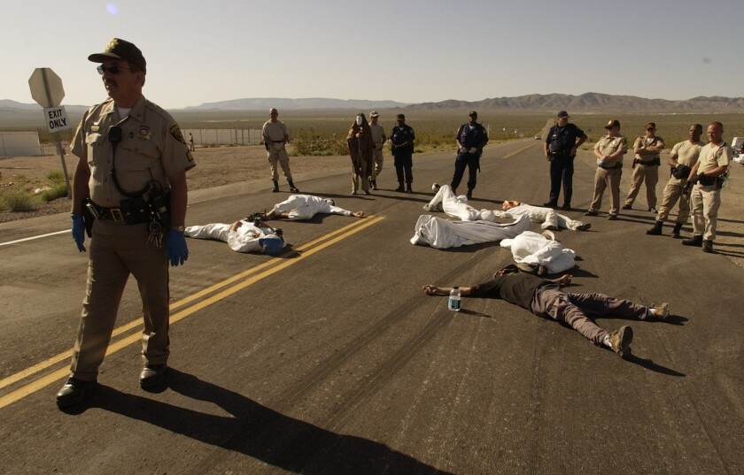 FILE - In this May 11, 2003, file photo, protesters lie on the pavement opposed to the proposed Yucca Mountain nuclear storage facility and weapons testing after crossing the line into the Nevada Test Site at Mercury, Nev., and were arrested for trespassing about 70 miles north of Las Vegas. A bipartisan group of lawmakers is renewing the push to expand a federal compensation program for radiation exposure following uranium mining and nuclear testing carried out during the Cold War. Advocates have been trying for years to bring awareness to the lingering effects of nuclear fallout surrounding the Trinity Site in southern New Mexico and on the Navajo Nation, where more than 30 million tons of ore were extracted over decades to support U.S. nuclear activities. (AP Photo/Joe Cavaretta,File)