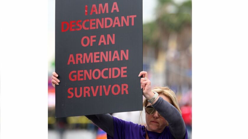 Vera Tchaghayan-Acun of Sun Valley holds a sign during the March for Justice commemorating the 100th