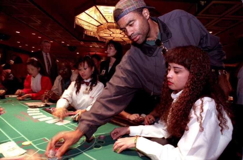 A man places a bet at a pai gow poker table at the Normandie Casino in Gardena, in a file photo.