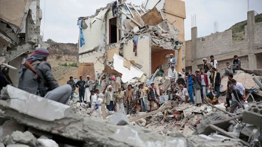 FILE - In this Aug. 25, 2017 file photo, people inspect the rubble of houses destroyed by Saudi-led