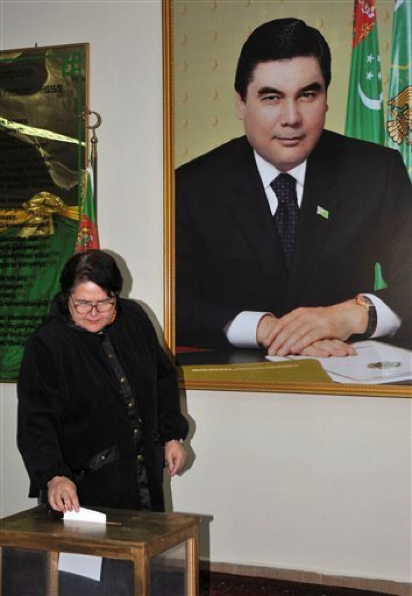 With a portrait of Turkmenistan President Gurbanguli Berdymukhamedov in the background a voter casts a ballot in a parliamentary election at a polling station in the capital Ashgabat, Sunday, Dec. 14, 2008. It was the first parliamentary election since the death of longtime autocrat Saparmurat Niyazov two years ago, which kindled hopes the Central Asian country would gradually loosen its oppressive political regime and introduce greater freedoms. Niyazov ruled Turkmenistan with an iron fist for almost two decades, isolating the international community and forging a bizarre personality cult. (AP Photo)