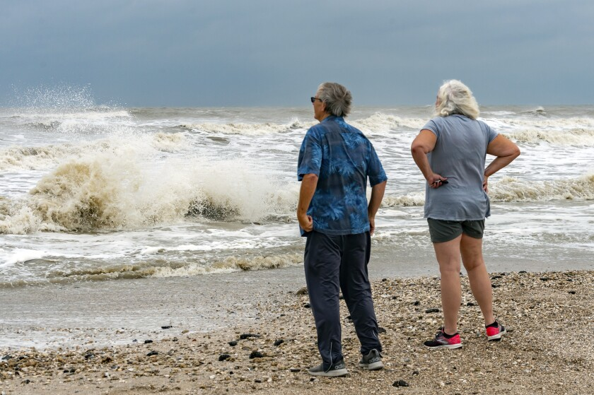 Steve and Linda Buser of Beaumont check out the rough surf on the beach near the intersection of Highway 124 and Highway 87 on the Bolivar Peninsula, Texas, Sunday, Sept. 20, 2020. Tropical Storm Beta was expected this week to bring heavy rainfall to parts of the upper Texas Gulf Coast and Louisiana, adding to the stress and worry residents and officials have already dealt with during a busy hurricane season. (Fran Ruchalski/The Beaumont Enterprise via AP)