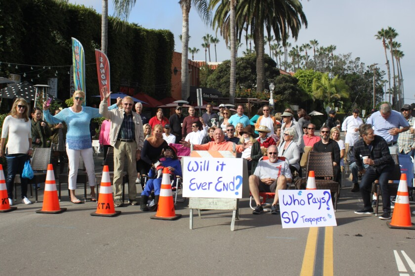 Dozens of Shores business owners and residents gather on a closed section of Avenida de la Playa Monday morning to protest what they see as a lack of City accountability during the three years of road construction they have endured.