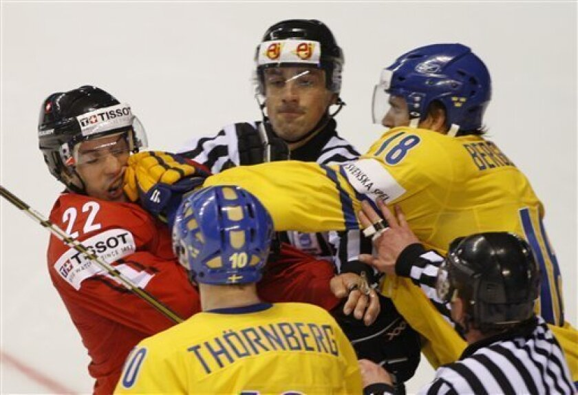 Sweden's Patrik Berglund, right, punches Victor Stancescu, left, from Switzerland during their qualification round group F Hockey World Championships match in Kosice, Slovakia, Sunday, May 8, 2011. (AP Photo/Petr David Josek)