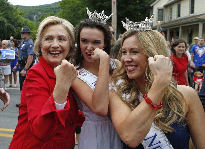 Hillary Clinton flexes her muscles with Miss Teen New Hampshire Allie Knault, center, and Miss New Hampshire Holly Blanchard during a campaign stop in the state this year.