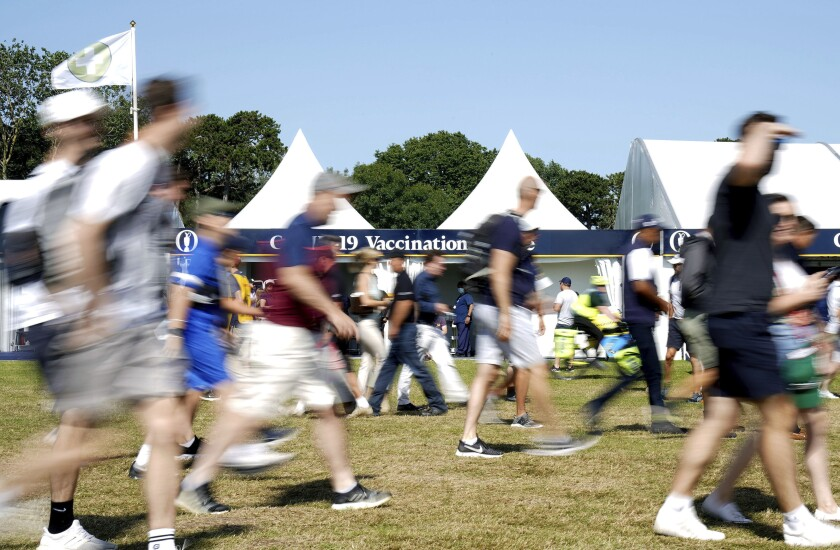 People walk by a COVID-19 vaccination centre on site, during day three of British Open Golf Championship, at the Royal St George's Golf Club in Sandwich, Kent, England, Saturday July 17, 2021. (Gareth Fuller/PA via AP)