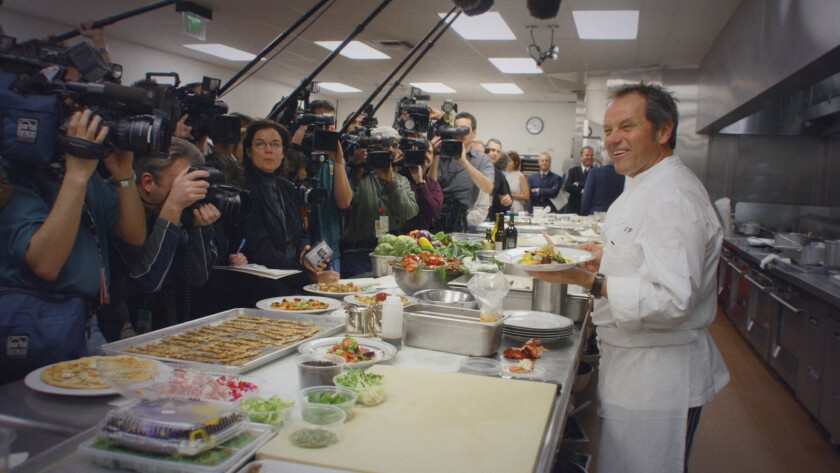 """A chef stands in his kitchen facing camerapeople and reporters in the documentary """"Wolfgang."""""""