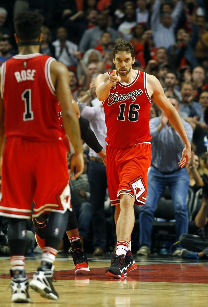 Chicago Bulls forward Pau Gasol (16) points to guard Derrick Rose (1) after Gasol scored a basket from a pass from Rose during the second half of an NBA basketball game against the Oklahoma City Thunder in Chicago, on Thursday, Nov. 5, 2015. The Bulls won the game 104-98. (AP Photo/Jeff Haynes)