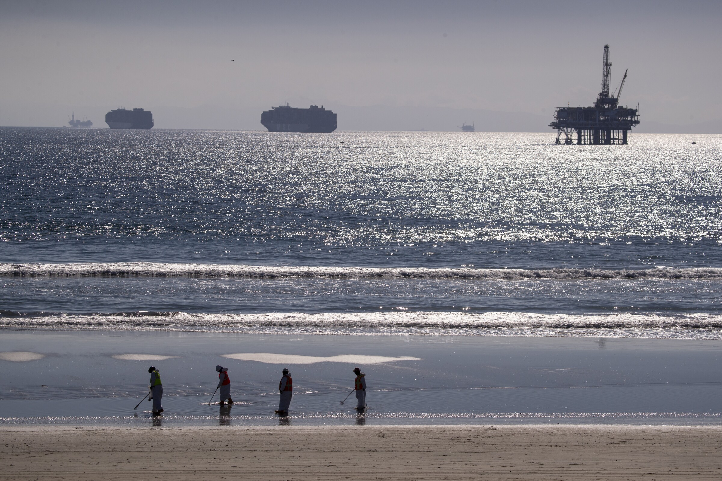 On the horizon, container ships and an oil derrick off Huntington Beach