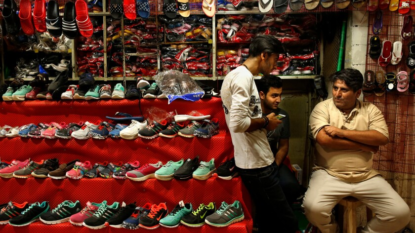 At the Grand Bazaar, Amir Khaledi, right, who owns a kiosk selling Iranian-made shoes and sandals, said he overwhelmingly supported President Hassan Rouhani's nuclear diplomacy as a way to end Iran's long estrangement with the West.