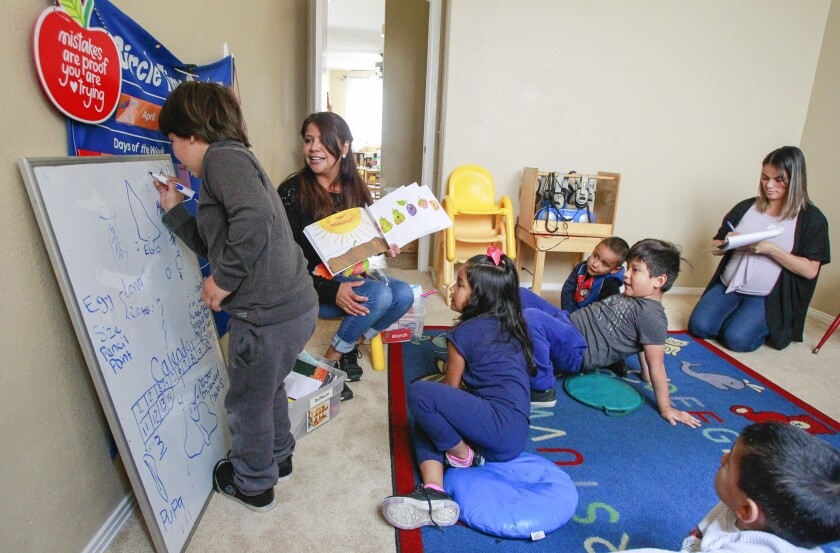 Teacher Elizabeth Garza (left) and YMCA Childcare Resource Service quality support specialist Marlene Fuentes (right) work with children during circle time on May 1, 2019 in Vista, California.