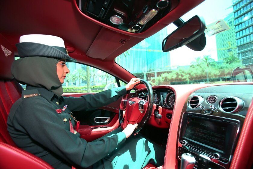 In this Thursday May 19, 2016 photo, Police officer Bodoor Jassim al Saffar takes the wheel of a Bentley Continental GT police car during a demonstration in Dubai, United Arab Emirates. Police in Dubai have built up a high-horsepower arsenal of luxury sports cars and SUVs over the years to compleme