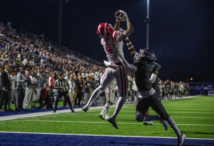 Receiver Kody Epps of Mater Dei catches a pass for a touchdown over Josh Alford of St. John Bosco. Both schools are in the Division 1 semifinals.