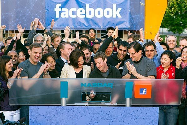 Mark Zuckerberg, chief executive officer of Facebook Inc., center, Sheryl Sandberg, chief operating officer of Facebook, center left, and Robert Greifeld, chief executive officer of Nasdaq OMX Group Inc., center right, remotely ring the opening bell for trading at the Nasdaq MarketSite from the Facebook campus in Menlo Park, Calif. Facebook Inc. began trading Friday after a record initial public offering that made the social network more valuable than almost every company in the Standard & Poor's 500 Index.