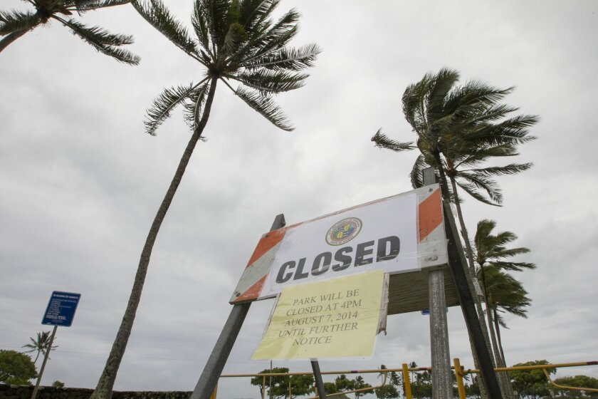 Winds from Tropical Storm Iselle blow palm trees near a sign warning of the closure of Kualoa Regional Park in Honolulu on Friday, Aug. 8, 2014. All of the public parks on Oahu were closed. Iselle came ashore onto the Big Island early Friday as a weakened tropical storm, while Hurricane Julio, behind it, is forecasted to pass north of the islands. Iselle is the first tropical storm to hit the state in 22 years. (AP Photo/Eugene Tanner)
