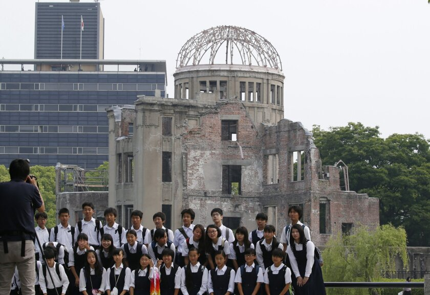 School children pose for a group photo with the Atomic Bomb Dome as a backdrop in Hiroshima Peace Memorial Park in Hiroshima, western Japan, Friday, May 27, 2016. Convinced that the time for this moment is right at last, U.S. President Barack Obama on Friday will become the first American president