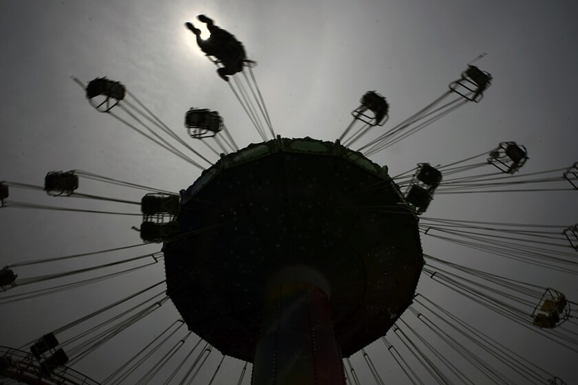 FILE - In this June 16, 2020, file photo, a lone visitor enjoys the swing ride at the Yomiuriland amusement park in Tokyo,. Japan's economy is opening cautiously, with social-distancing restrictions amid the coronavirus pandemic. (AP Photo/Eugene Hoshiko, File)