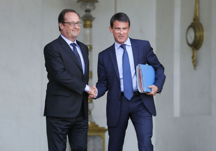 French President Francois Hollande and Prime Minister Manuel Valls shake hands at the Elysee Palace in Paris on Aug. 20.