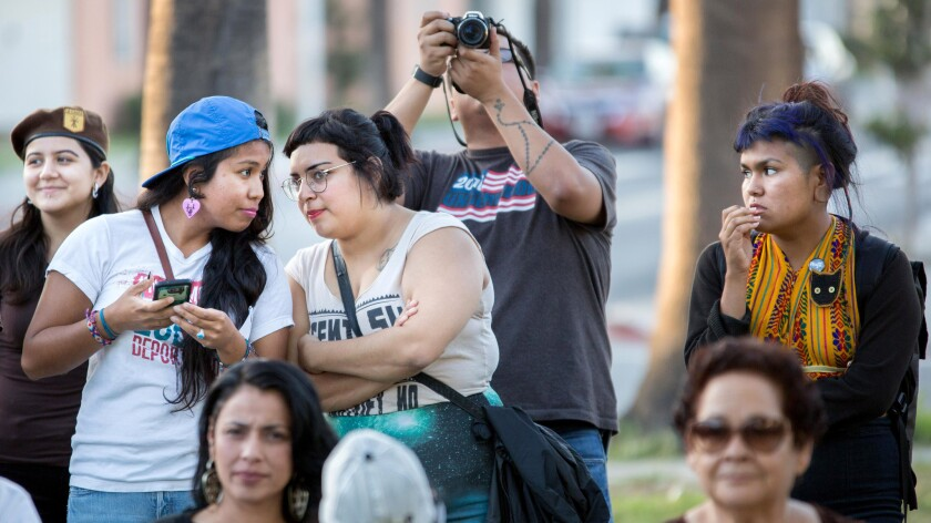 Maga Miranda, center,  a member of Defend Boyle Heights, attends a community meeting at Pico Gardens in Boyle Heights.