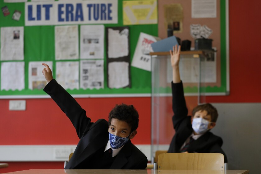 Year seven pupils Henry Holness, left, and Eddie Favell in class during their first day at Kingsdale Foundation School in London, Thursday, Sept. 3, 2020. Schools in England are starting to reopen with special measures in place to deal with Coronavirus. (AP Photo/Kirsty Wigglesworth)