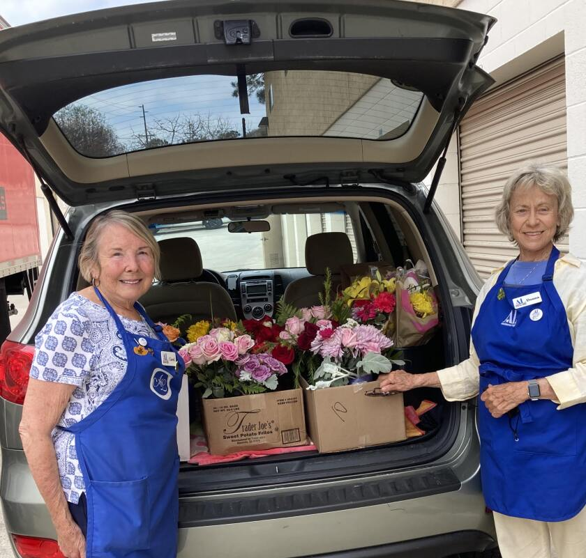 Carol Tuggey and Donna Buys load bouquets for delivery