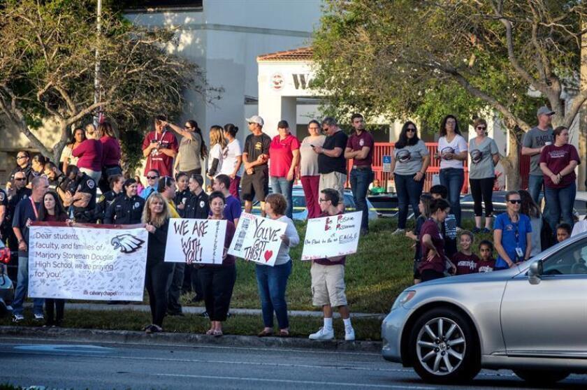 Varias personas sostienen pancartas de apoyo a padres y estudiantes mientras llegan a la escuela Marjory Stoneman Douglas en Parkland, estado de Florida (Estados Unidos). EFE/Archivo
