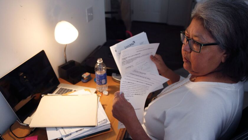 A Californian sifts through the paperwork of her numerous high interest loans at the desk in her apartment in Rancho Santa Margarita in January 2016.