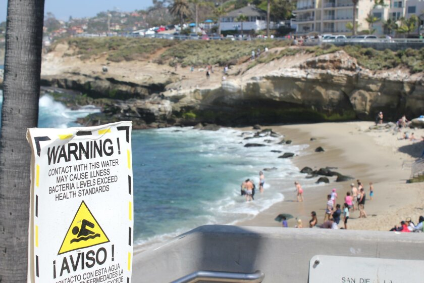 Beachgoers continue to enter the ocean at La Jolla Cove despite warning signs posted by county health officials.