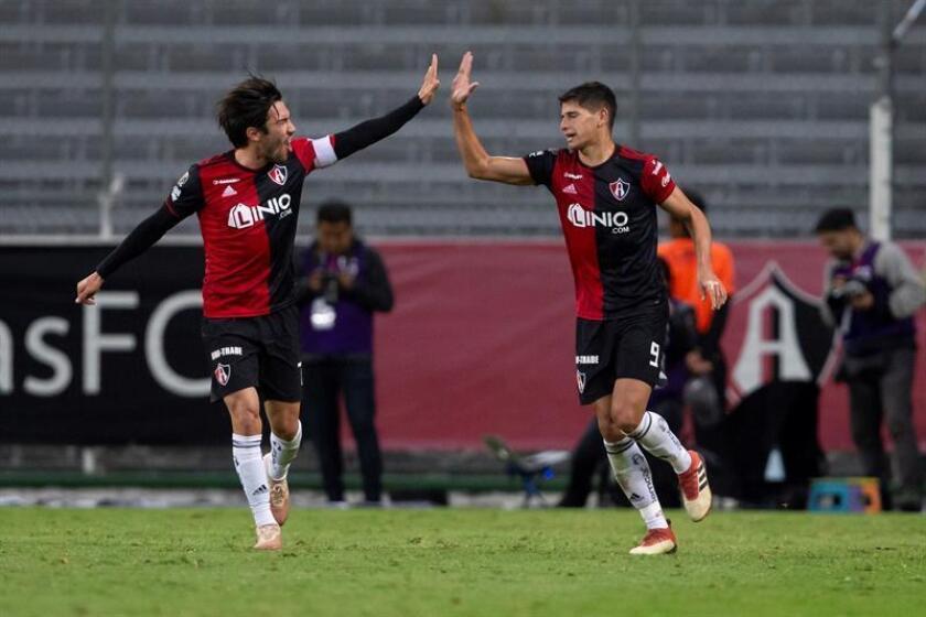 El jugador de Atlas Juan Vigón (i) y Facundo Barceló (d) celebran una anotación el 25 de enero de 2019 ante Lobos BUAP, durante el juego correspondiente a la jornada 4 del torneo mexicano de fútbol, celebrado en el estadio Jalisco, en la ciudad de Guadalajara (México). EFE/Archivo