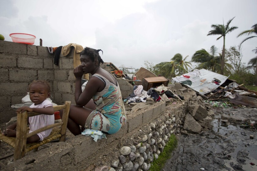Victor Farah and her daughter sit in the ruins of their home, destroyed by Hurricane Matthew, in Les Cayes, Haiti, on Thursday.