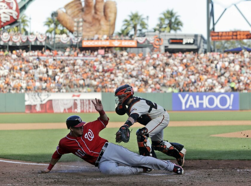 Washington Nationals Wilson Ramos (40) scores past the tag of San Francisco Giants catcher Buster Posey in the seventh inning during Game 3 of baseball's NL Division Series in San Francisco, Monday, Oct. 6, 2014.(AP Photo/Marcio Jose Sanchez)