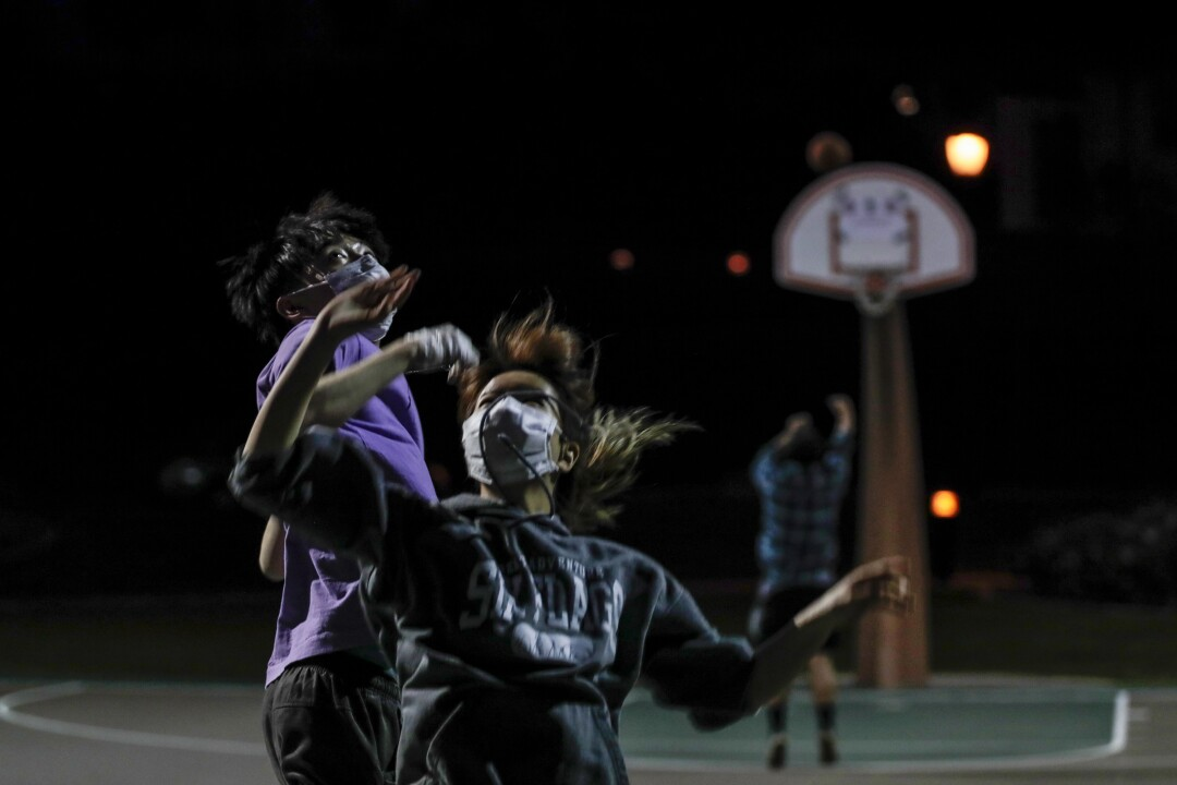 Young friends play a spirited game of basketball in Azusa despite posted warnings about the coronavirus.