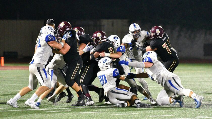 Bronco defenders Luke Manos, Alex Florey and Jacob Wiggins wrap up a Point Loma running back during