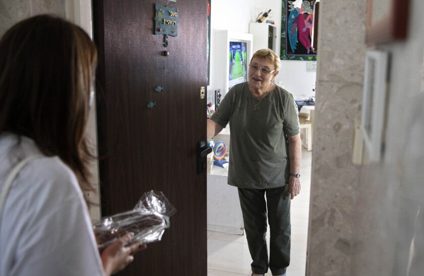 Israeli volunteer Sharon Yaron, left, brings a cake to 85-year-old Holocaust survivor Sara Weinsten during a visit to her house in Yavne, Israel, Thursday, Oct. 8, 2020. For thousands of older Israelis like Weinsten, being housebound alone during Israel's second nationwide lockdown due to the coronavirus pandemic is difficult and depressing. But each week ahead of the Jewish Sabbath, which starts on Friday at sundown, a home-baked cake is delivered by one of thousands of volunteers bringing pastries to home-bound older Israelis. (AP Photo/Sebastian Scheiner)