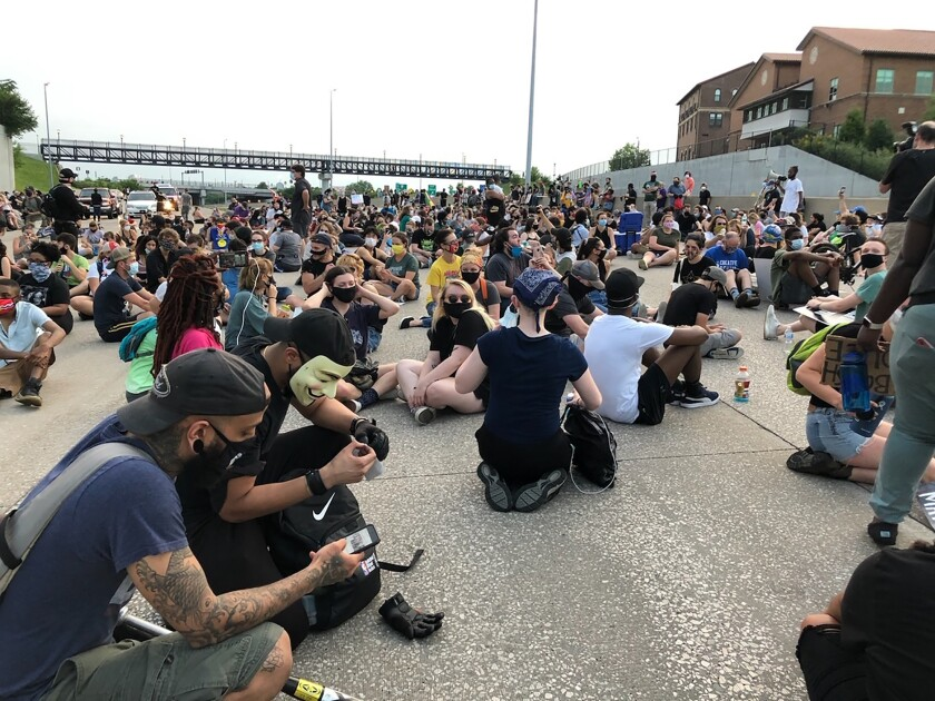 Protesters sit on Interstate 64 in St. Louis for several moments, Friday, July 3, 2020, in memory of George Floyd. The protest, the latest organized by the group Expect Us, was among several protests in the weeks since Floyd's death in Minneapolis reopened long-standing concerns about police treatment of Black people in the United States. Police closed the interstate to traffic in both directions and allowed the protesters to walk onto the highway. (AP Photo/Jim Salter)