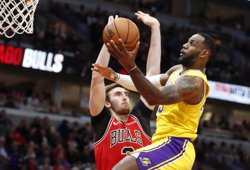Lakers star LeBron James, right, puts up a shot in front of Chicago Bulls forward Luke Kornet.