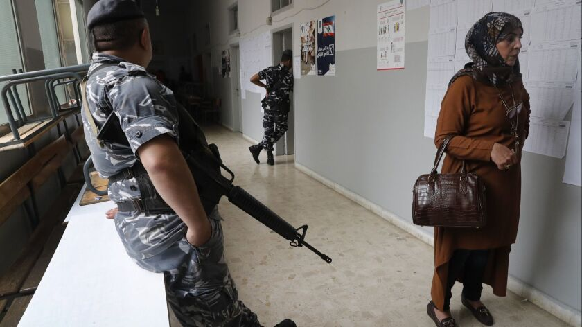 A policeman stands guard as a voter waits to cast her vote in Lebanon's parliamentary elections, in