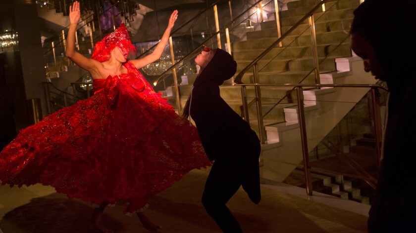 """Clad in red, Rachel Hernandez dances as part of the Viver Brasil Dance Company's staging of """"Revealed"""" on the staircase of the Dorthy Chandler Pavilion."""
