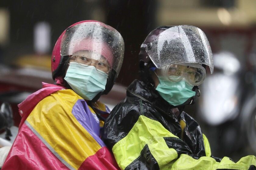 People ride a motorbike in the rain caused by Typhoon Chanthu in Taipei, Taiwan, Sunday, Sept. 12, 2021. Typhoon Chanthu drenched Taiwan with heavy rain Sunday as the storm's center passed the island's east coast heading for Shanghai. (AP Photo/Chiang Ying-ying)
