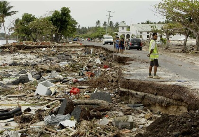 A beach-side road is half destroyed as debris litters the sand at Lalomanu, Samoa, as they search for bodies, Wednesday, Sept. 30, 2009, a day after a deadly tsunami rolled through several South Pacific island nations. A earthquake centered about 120 miles (193 kilometers) south of the islands of Samoa and American Samoa, triggered the tsunami early Tuesday. (AP Photo/Rick Rycroft)