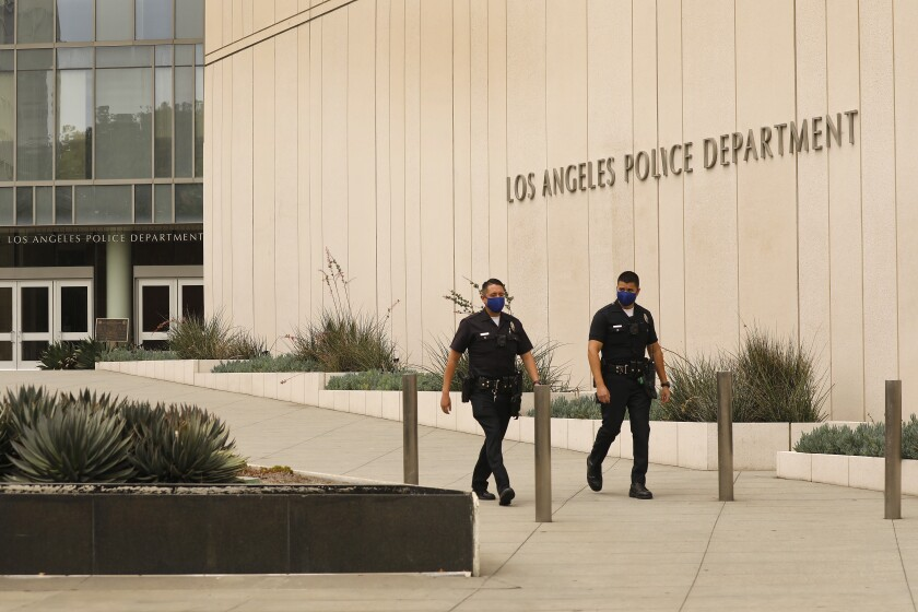 Two police officers walk outside LAPD headquarters