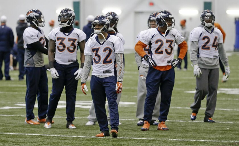 Denver Broncos defensive players Duke Ihenacho (33), Tony Carter (32), Quentin Jammer (23) and Champ Bailey (24) wait to begin a drill during practice Friday, Jan. 31, 2014, in Florham Park, N.J. The Broncos are scheduled to play the Seattle Seahawks in the NFL Super Bowl XLVIII football game Sunda